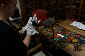 Conni films the shawl and piece of the fence, which are placed on the table in Special Collections at Bristol University