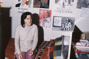 Ellen Malos sits on the bed in the women's centre. Women's Liberation posters adorn the walls