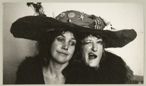 Two women sit under a giant hat, one pulls a funny face, both look mischeivous