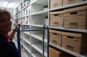 Sarah, project archivist, stands in front of archive boxes on a shelf